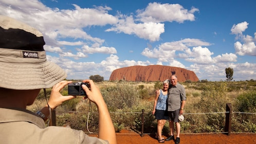Tour guide takes picture of couple in front of Uluru