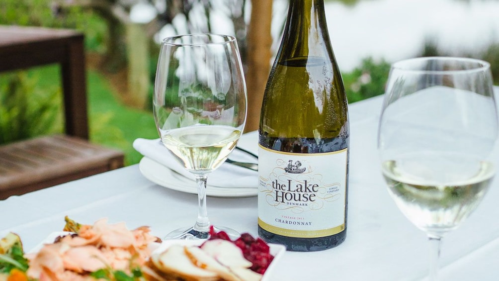 Bottle of wine with glasses and cuisine at The Lake House restaurant in Denmark, Australia
