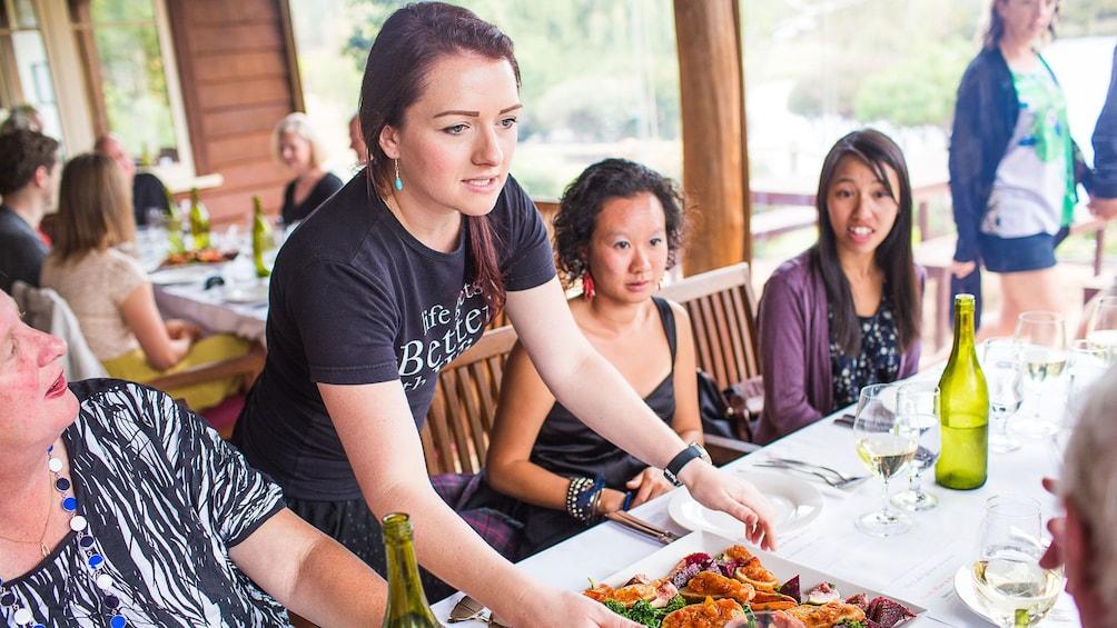 Waitress placing food on table at The Lake House restaurant in Denmark, Australia