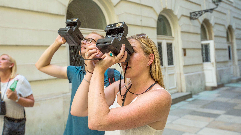 Couple taking polaroid photos on the Vienna State Opera tour