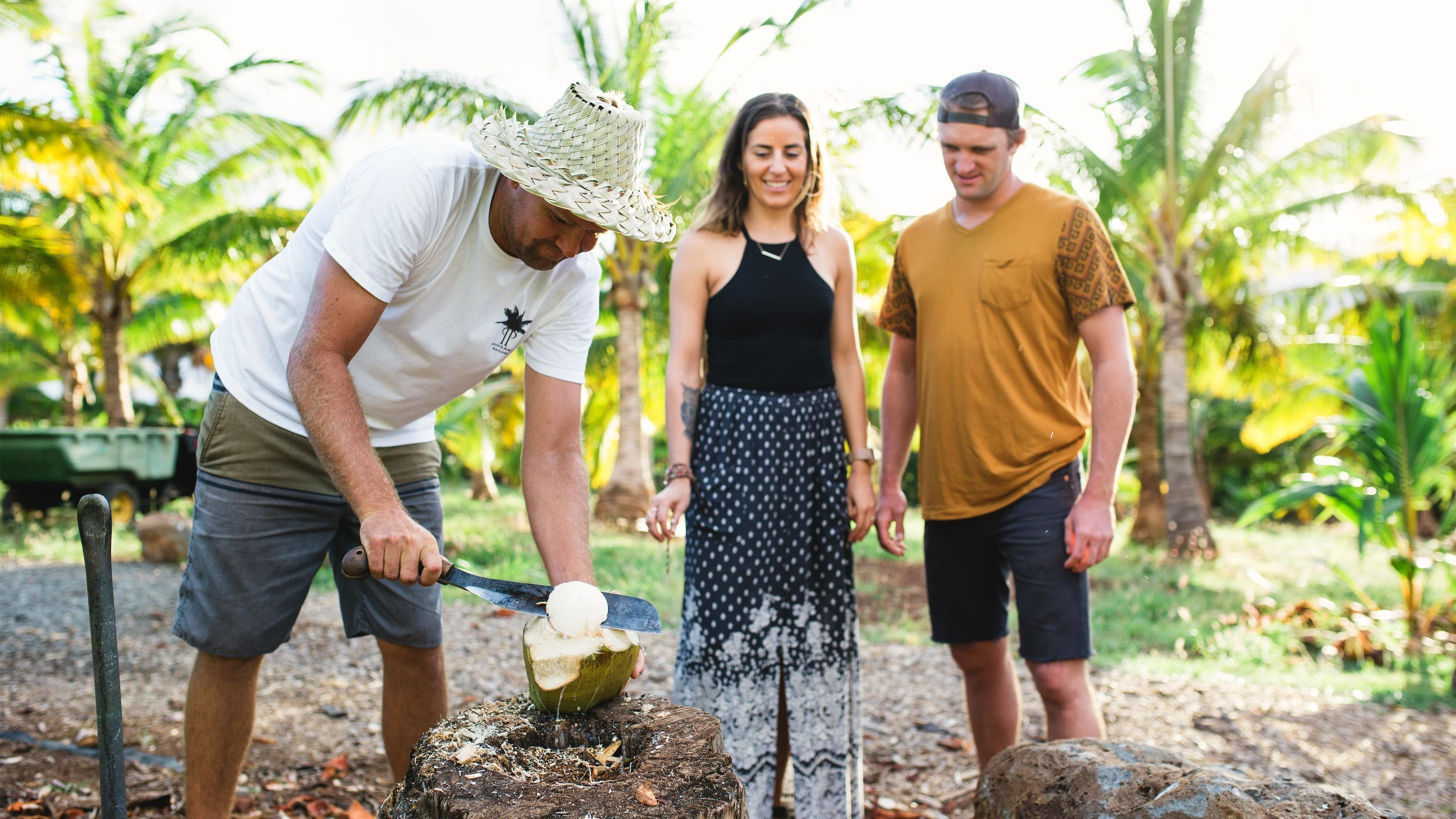 Man showing tourists how to slice open a coconut on a farm on Maui