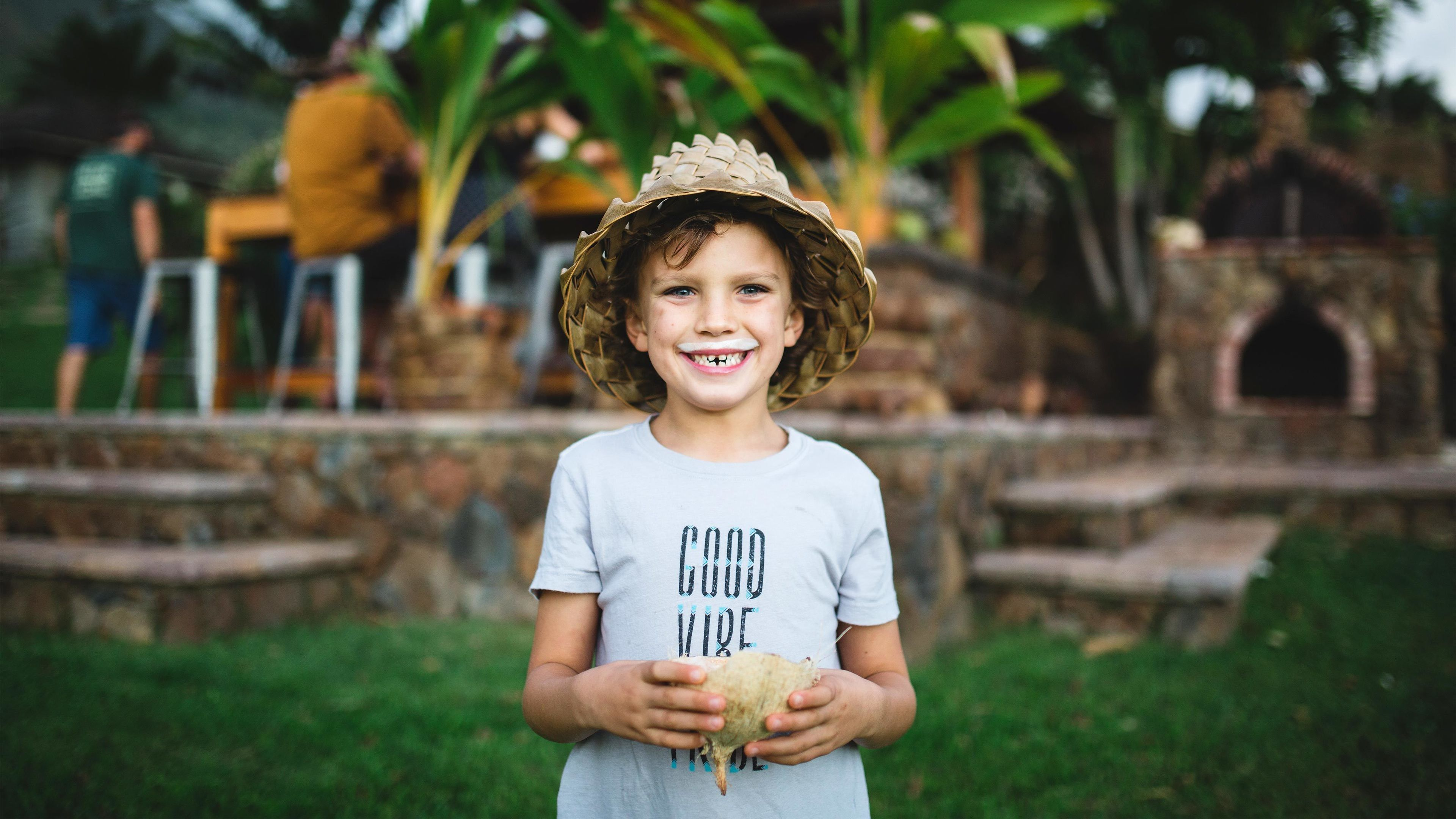 Smiling girl with a coconut milk mustache on a farm on Maui