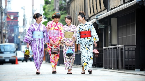 Group of 4 women in kimonos walking down street in Kyoto