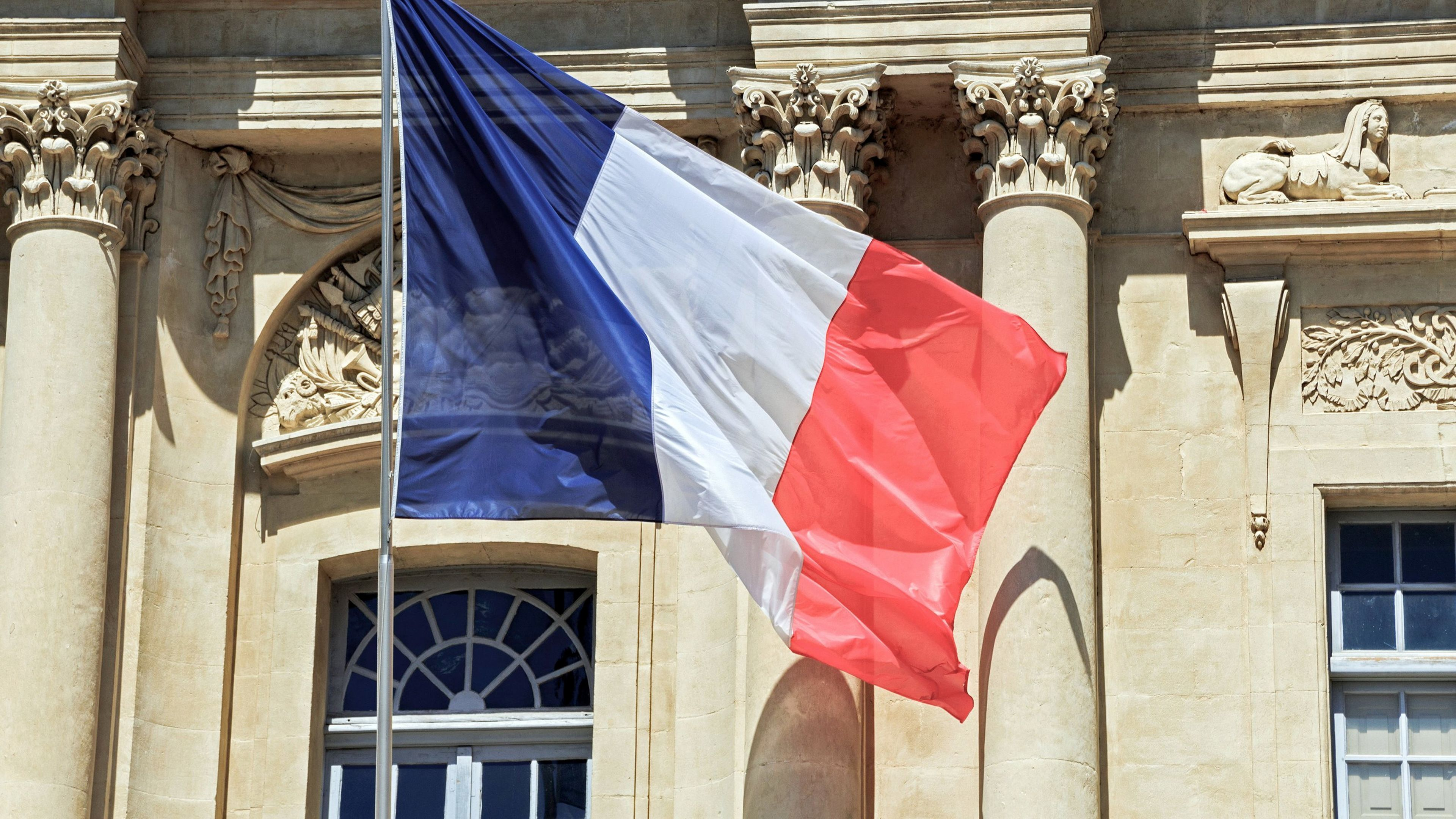 French flag and historic building in Paris