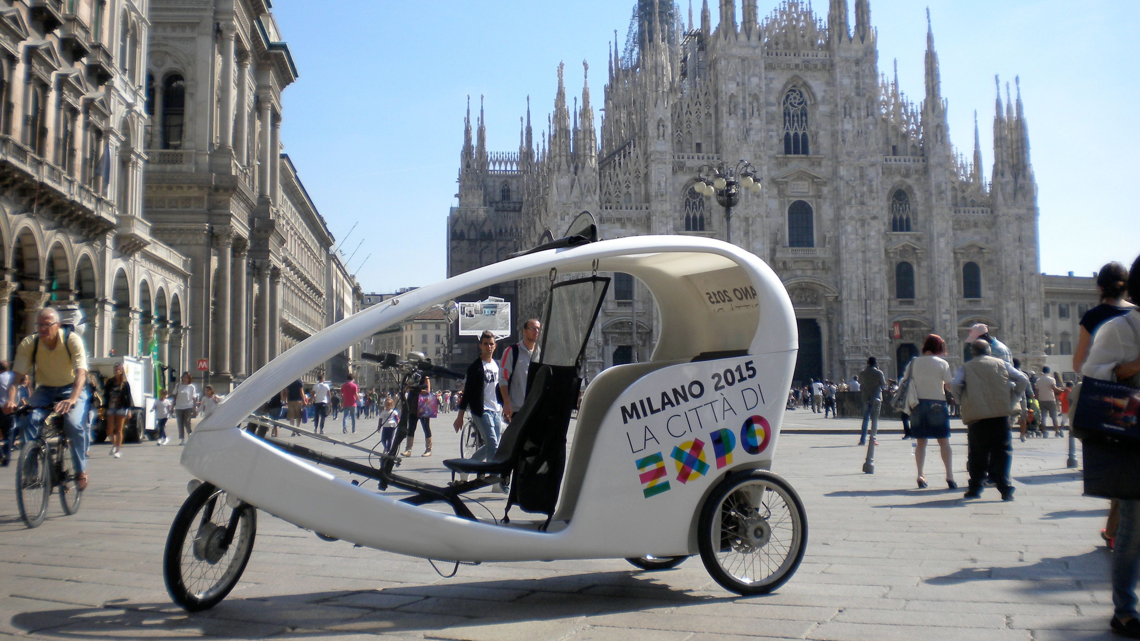 Rickshaws with a cathedral in the background in Milan