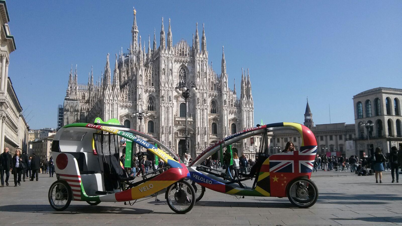 Pair of rickshaws with cathedral in the background in Milan
