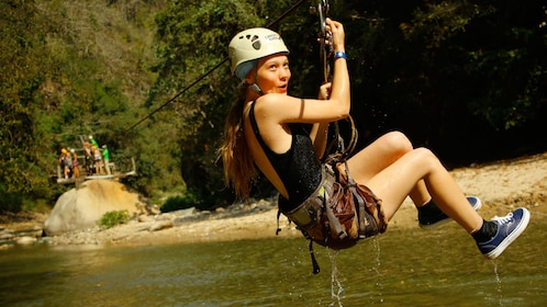 Young woman ziplining over a river in Puerto Vallarta