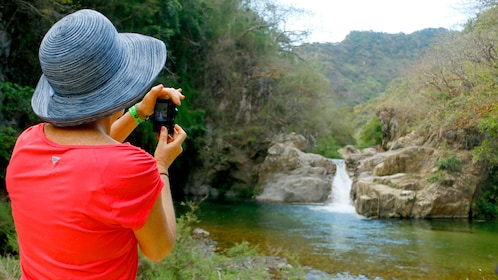 Woman taking a picture of waterfall