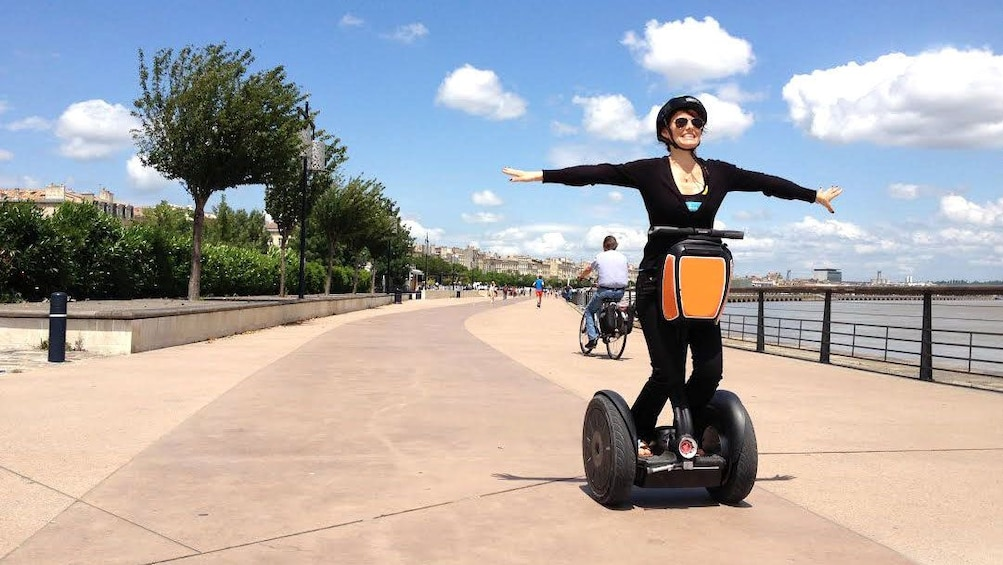 Charger l'élément 1 sur 5. Woman with arms stretched out to her sides on segway in Bordeaux