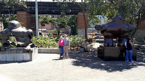 Couple standing between large sculptures in Medellin