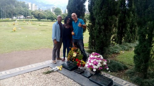 Tourists standing next to grave markers in Medellin