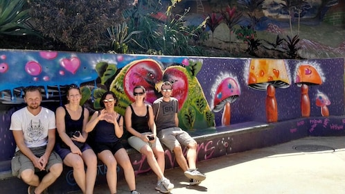 Tour group on a bench with colorful graffiti in Medellin