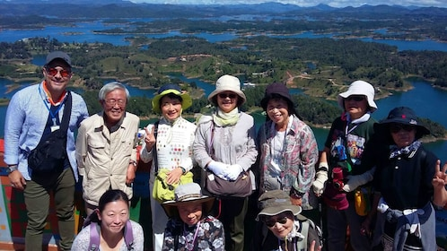 Tour group poses for photo with view of islands in background in Medellin