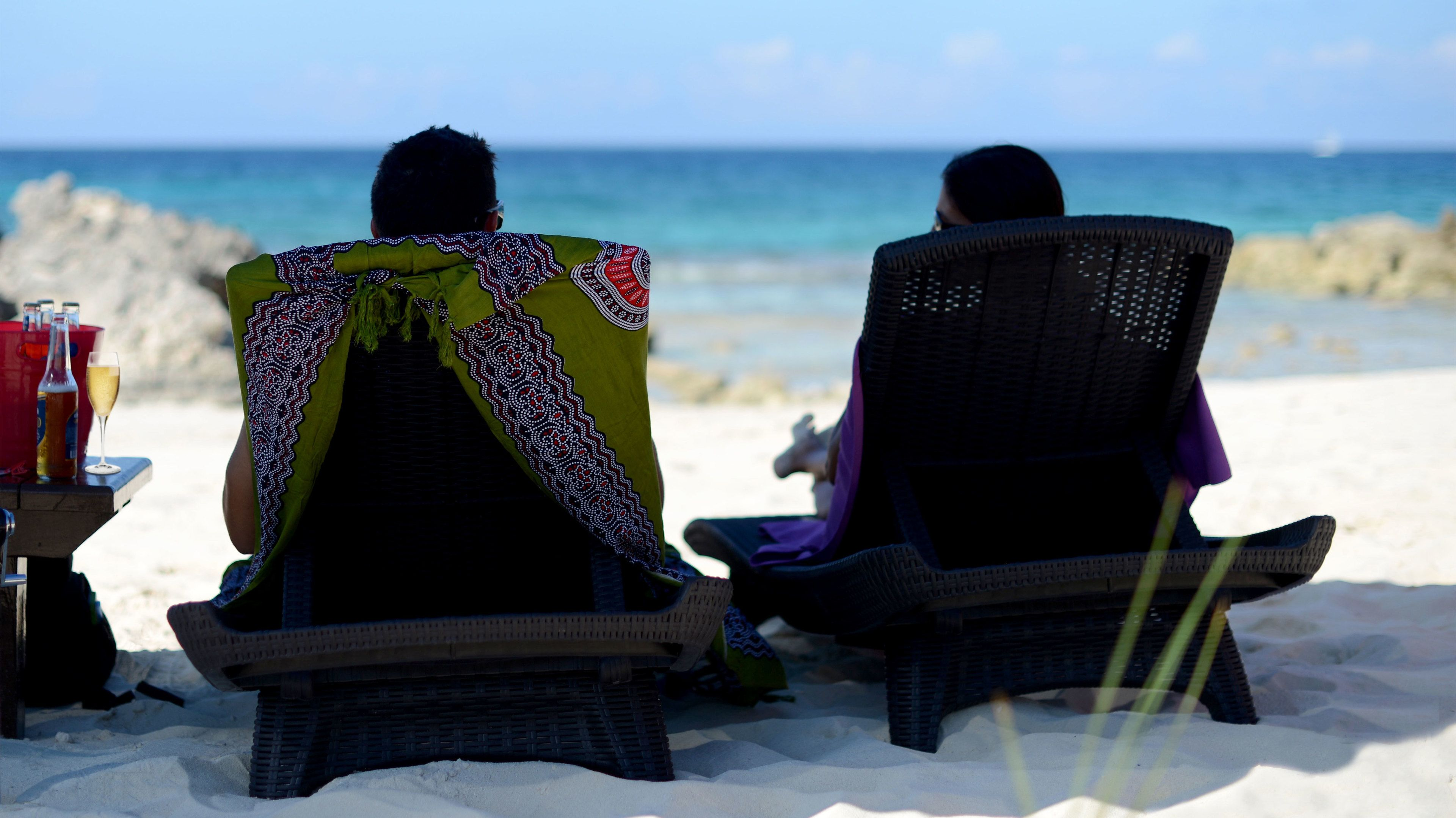 Couple lounging in chaise lounges on a beach in Grand Bahamas