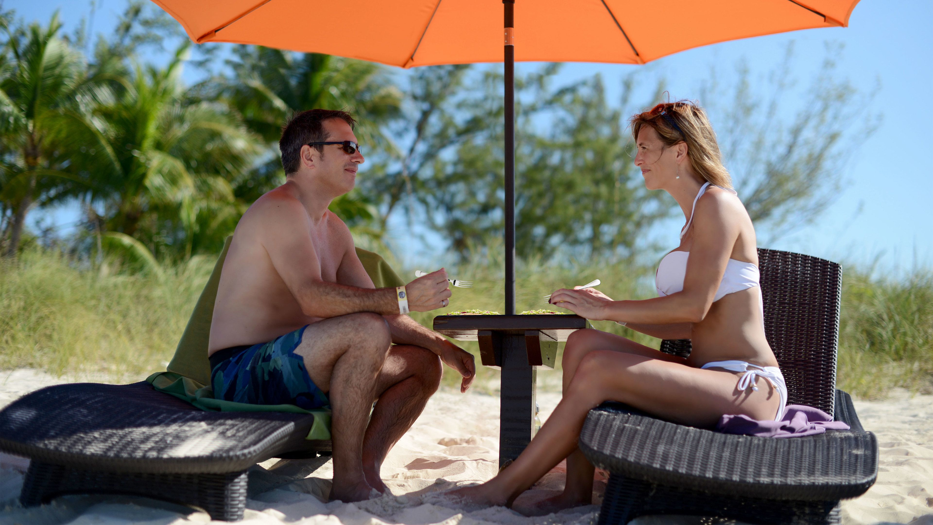 Couple with food on the beach in Grand Bahamas