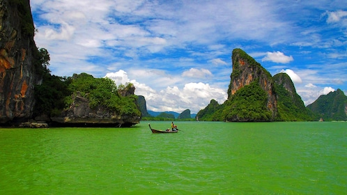 Person paddles boat in green waters of Thailand