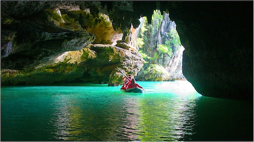 Tourists in Kayak paddle into dark cave in Thailand