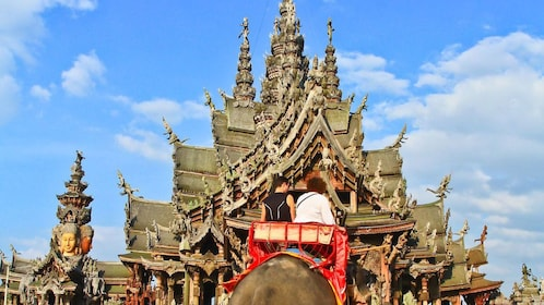 People ride elephant towards The Sanctuary of Truth in Pattaya