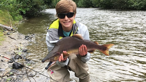 Young fisherman holds up salmon in Denali National Park