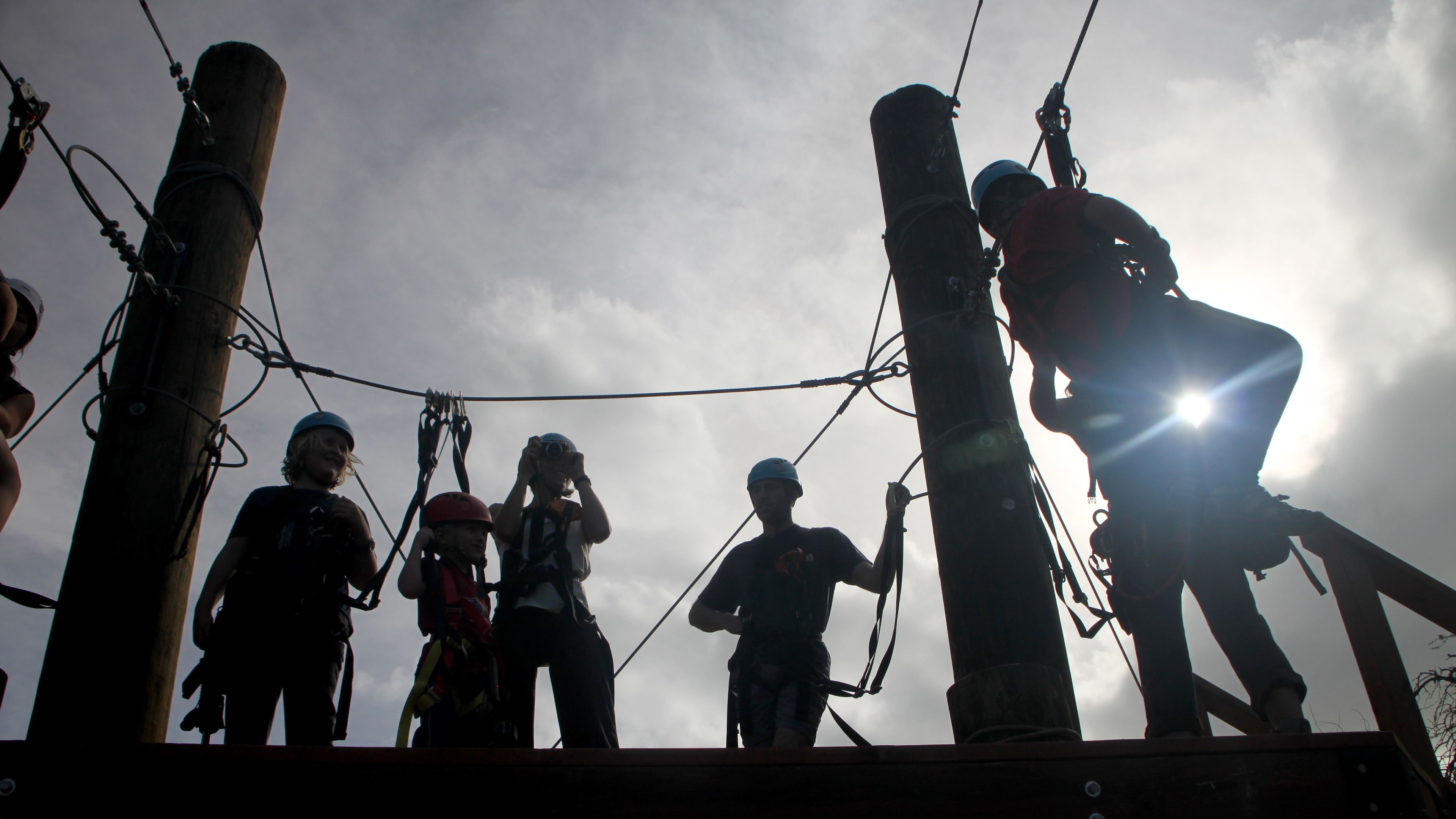 Silhouette of ziplining group on the launch platform on Oahu