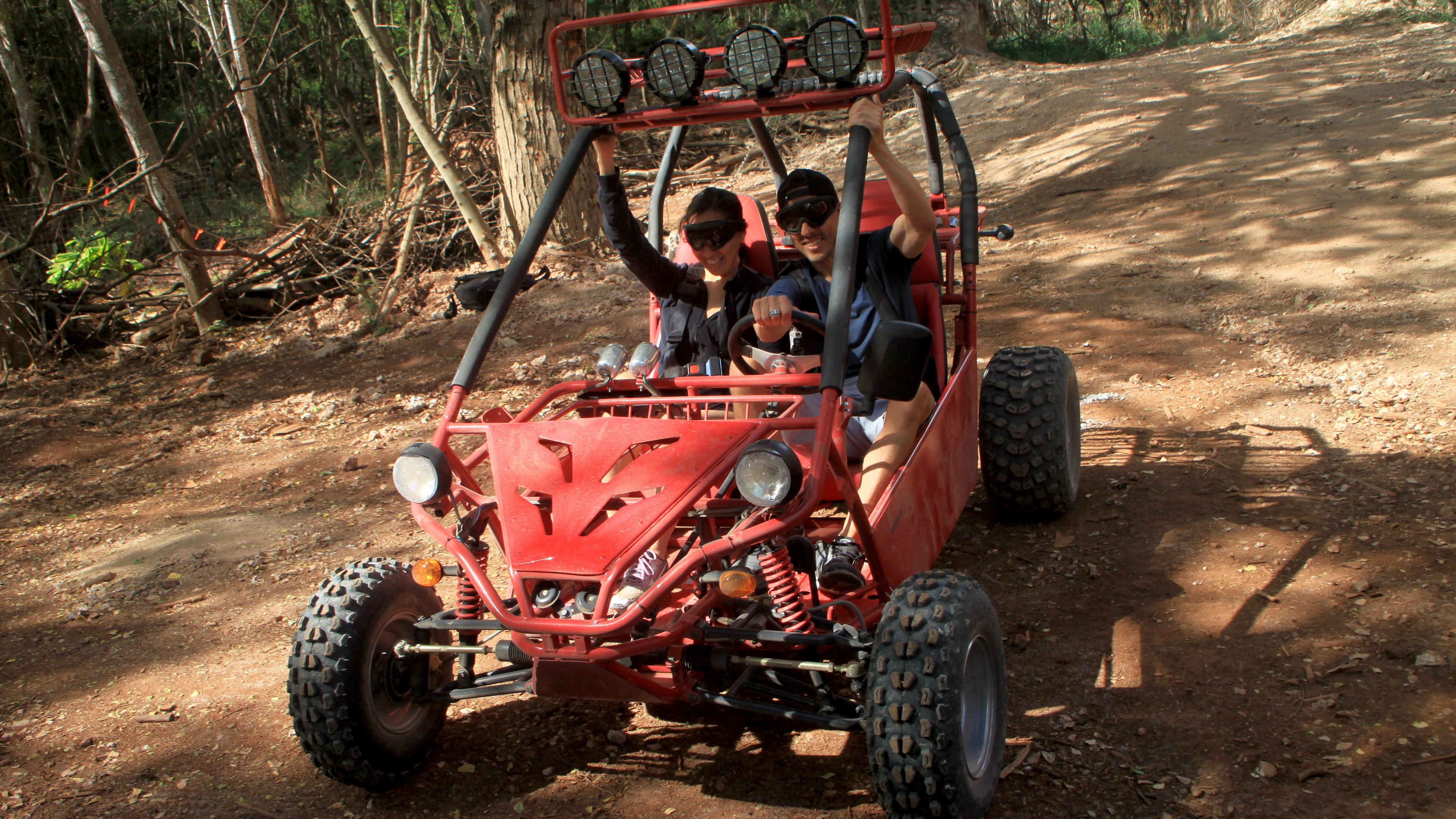 Couple driving an ATV on a dirt road on Oahu