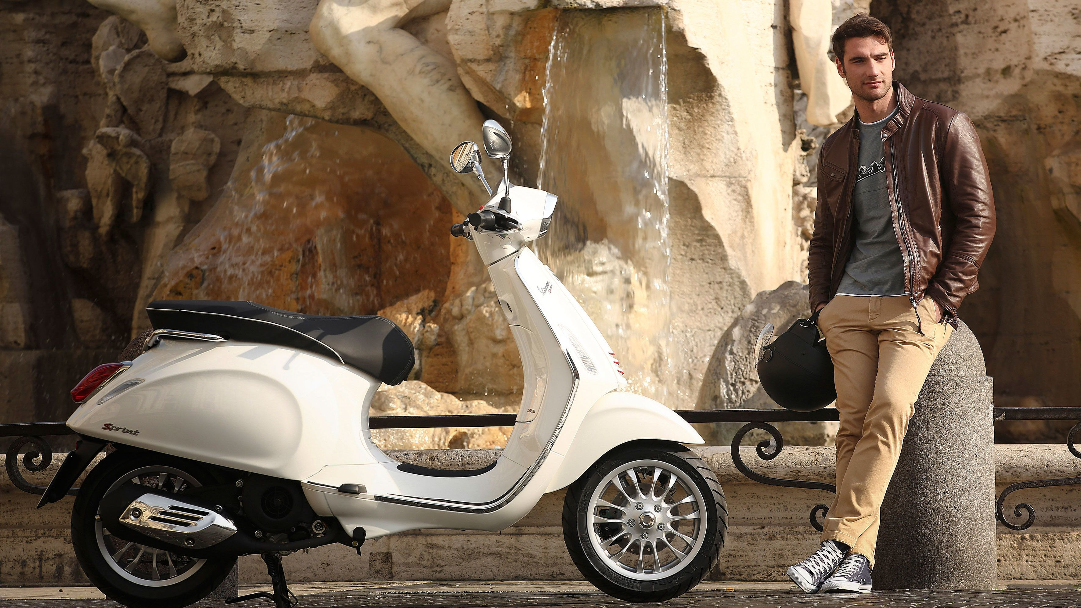 Man standing next to Vespa at a fountain in Rome