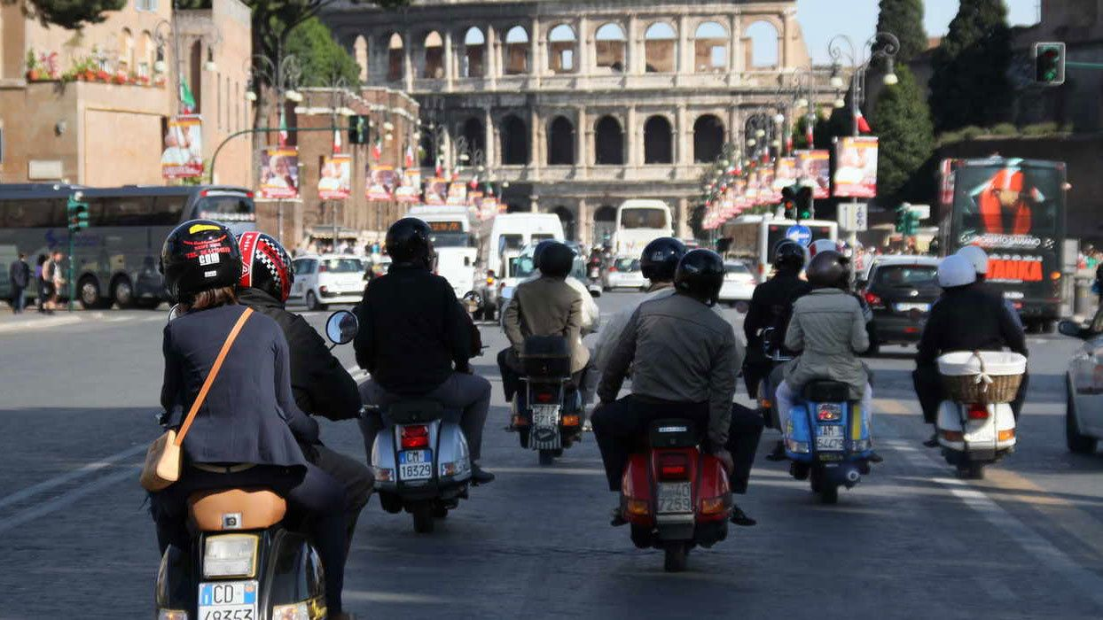 Group of Vespa riders near the Colosseum in Rome