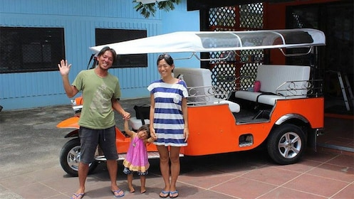 Family in front of Tuk Tuk vehicle on Cook Islands