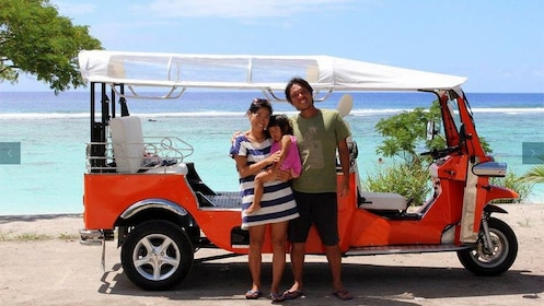 Family in front of Tuk Tuk vehicle on the coast of Cook Islands