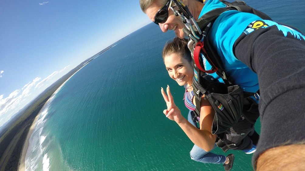 Skydivers with parachute deployed over Batemans Bay