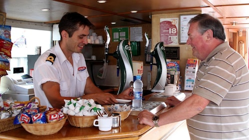 Man at food counter on small cruise boat in York