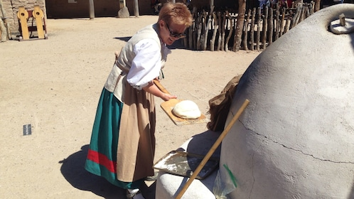 Woman in time period clothing places dough into wood burning oven in Presidio San Agustín del Tucson Museum