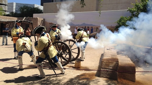 Men in time period clothing fire cannon at Presidio San Agustín del Tucson Museum