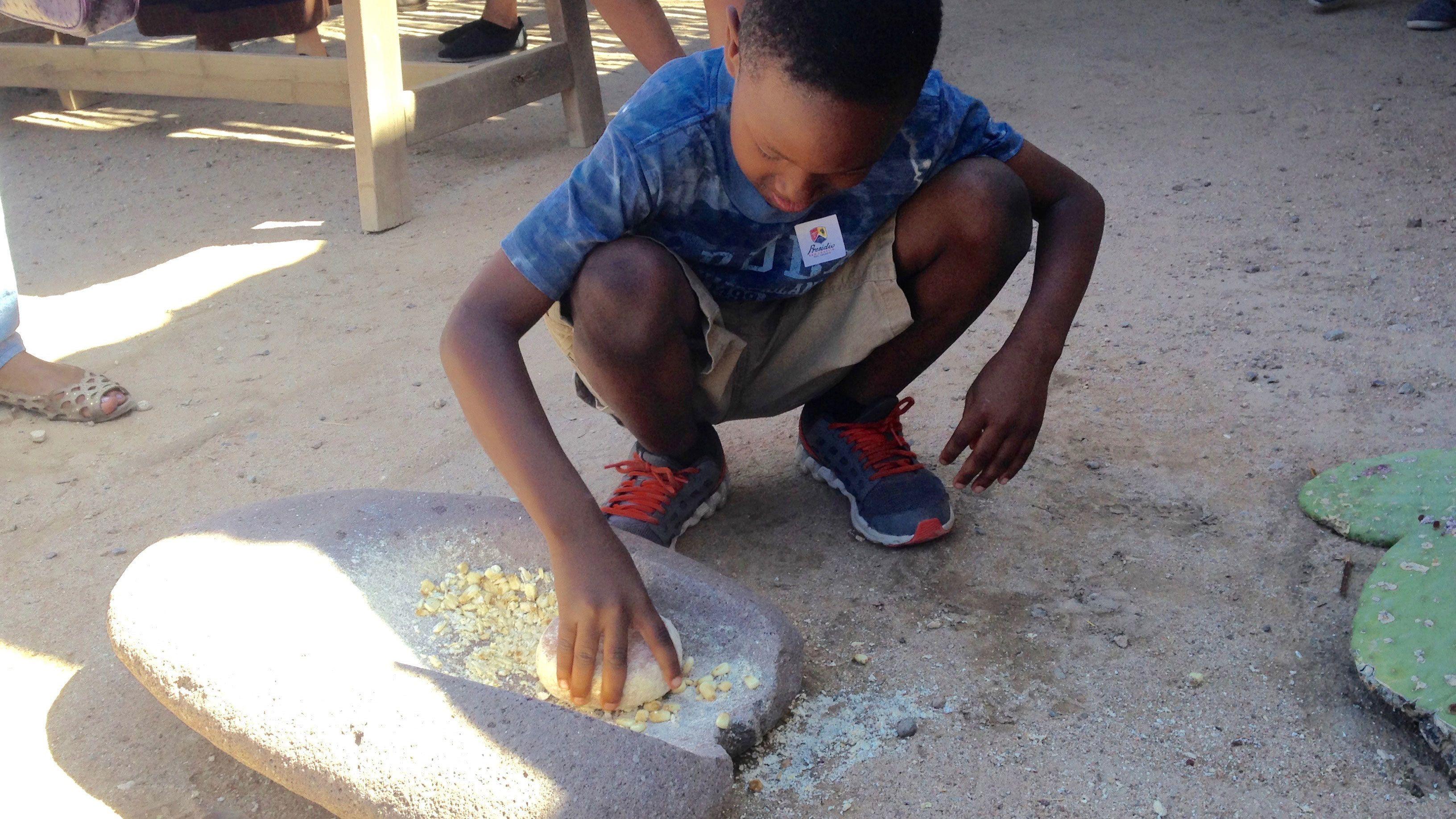 Young boy smashes grain into masa with stone at Presidio San Agustín del Tucson Museum