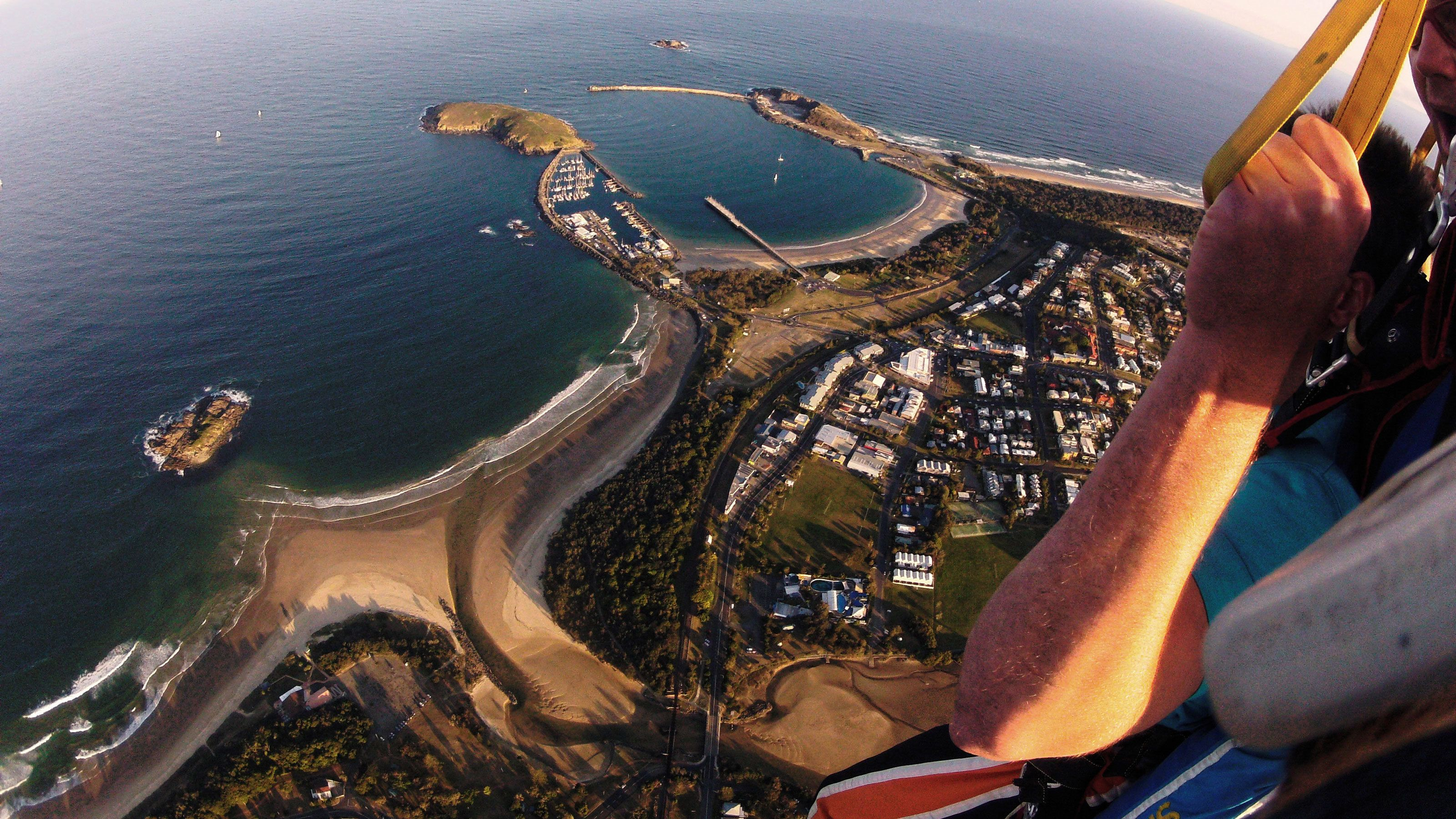 Tandem skydivers fly over Coffs Harbour after deploying parachute in Australia