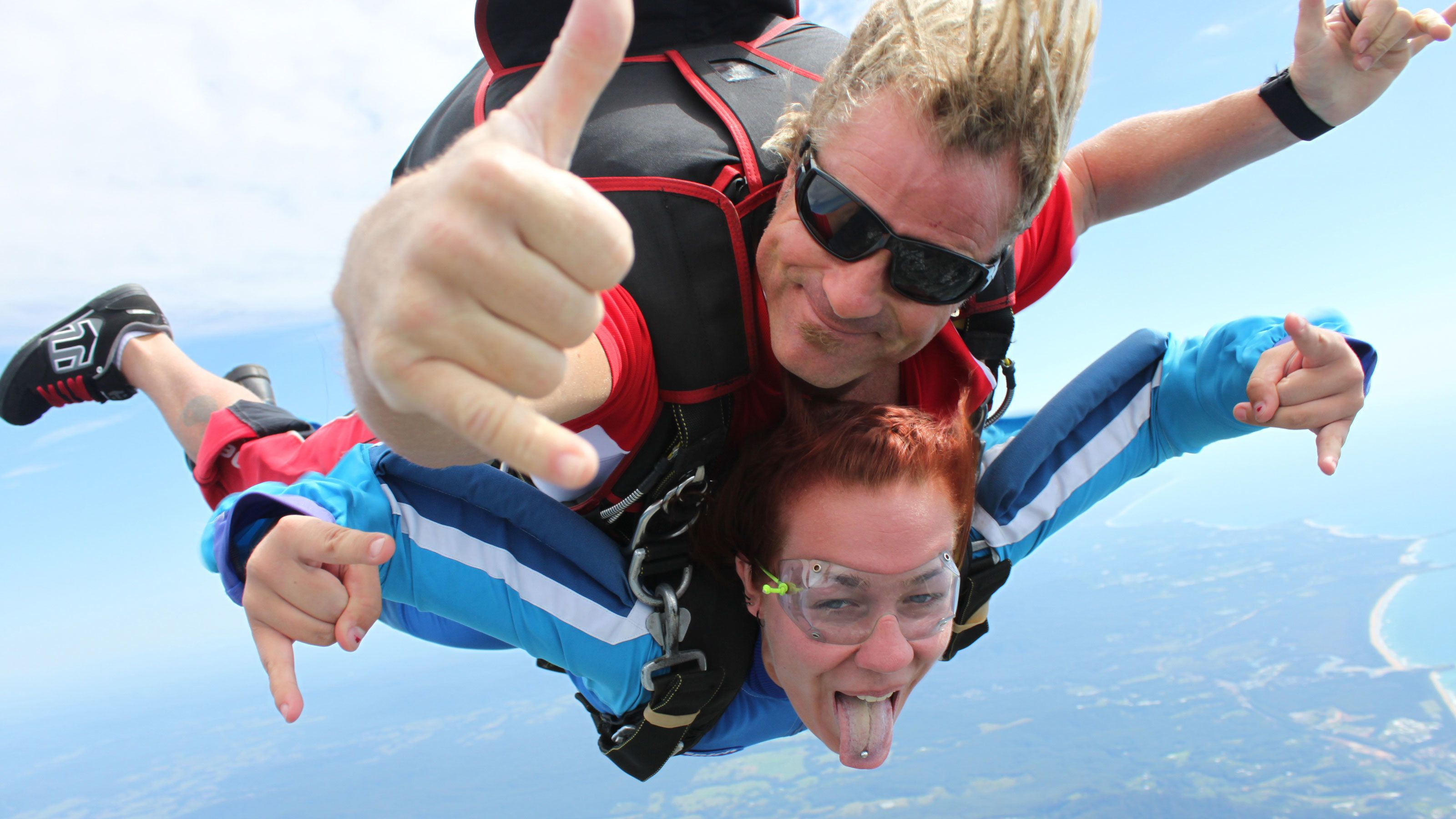 Couple making hang loose sign while on the Tandem Skydive Experience over Coffs Harbour in Australia