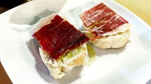 Bread with meat and olive oil during tasting in Seville
