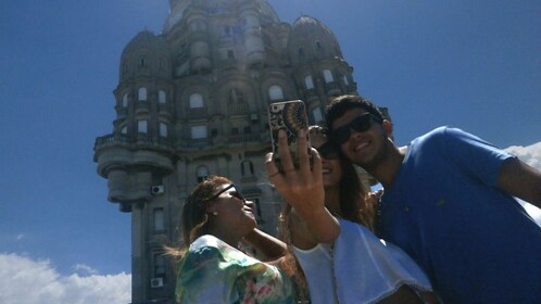Couple taking a selfie in front of tall building in Uruguay