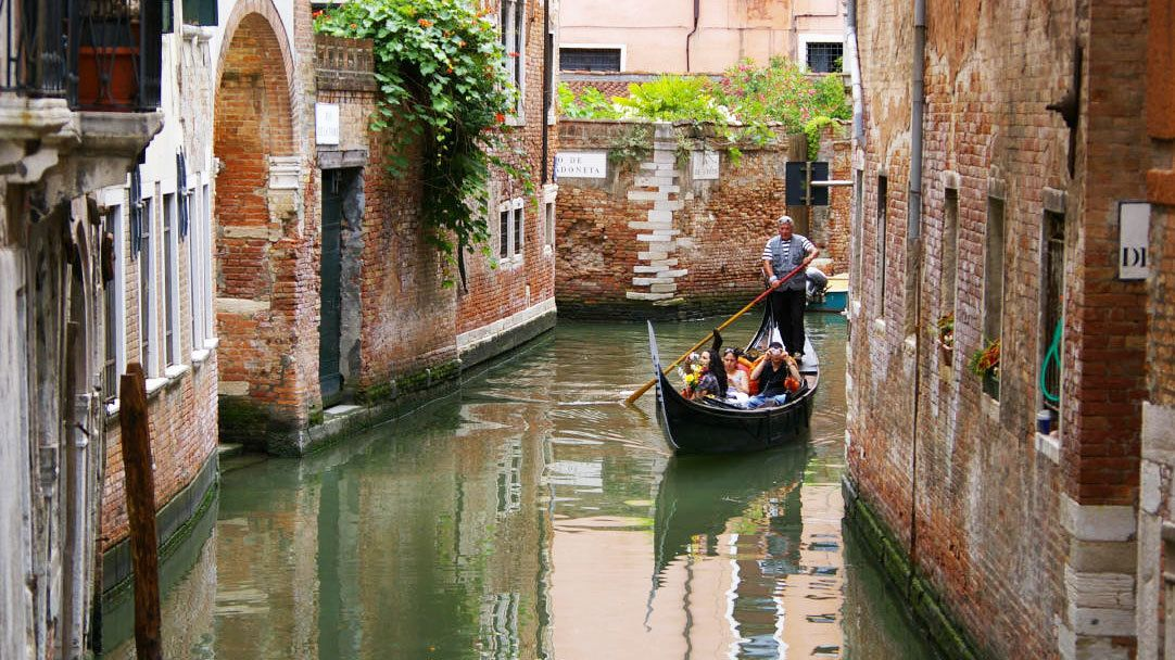 Single gondola paddles down quiet waterway in Venice