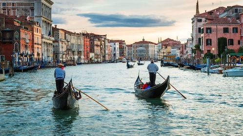 Two gondolas paddling down waterway in Venice