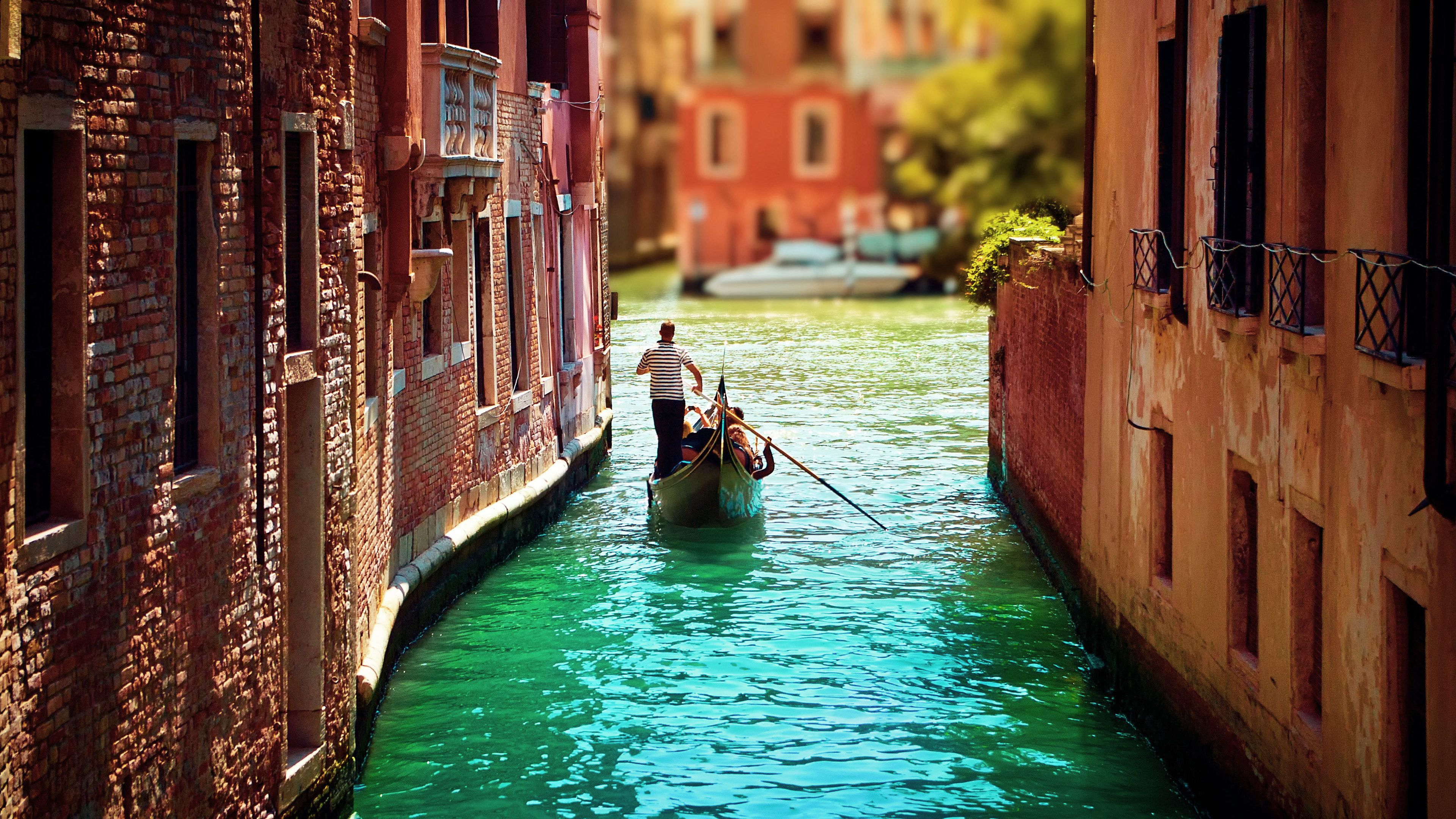 Single gondola paddles down narrow waterway in Venice