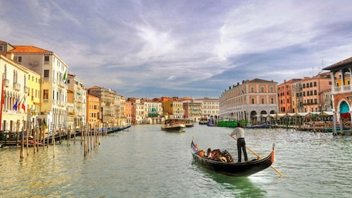Single gondola paddles down waterway in Venice
