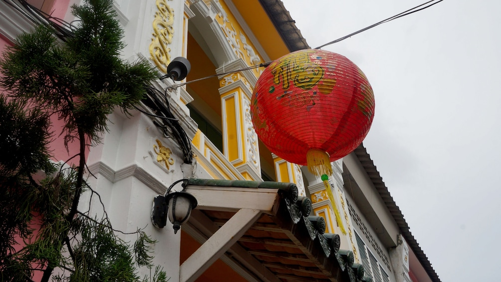 Show item 3 of 4. Paper lantern hanging from a building in Phuket