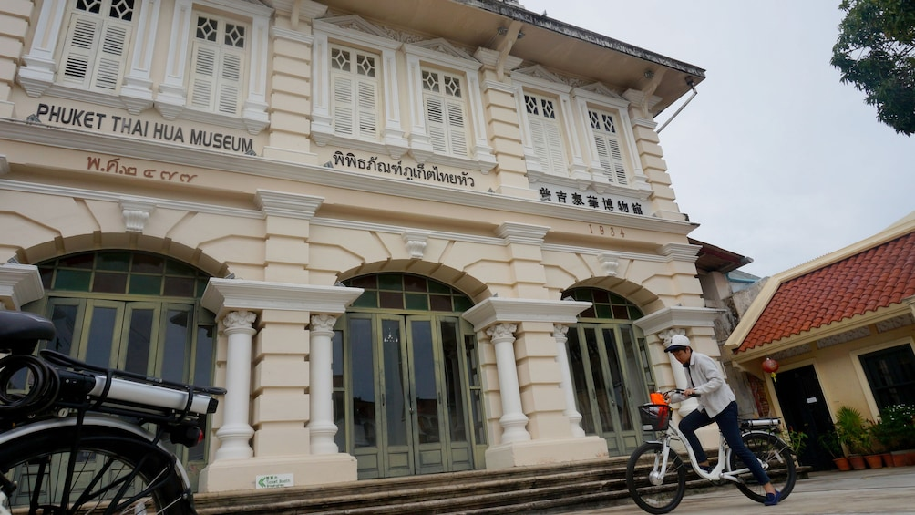 Show item 1 of 4. Man on bicycle outside museum in Phuket
