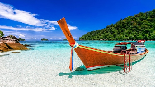 Boat moored at beach of Koh Lipe Island on snorkel tour in Malaysia