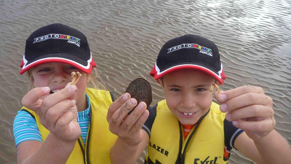 Show item 5 of 7. Children hold up their findings while out kayaking in Batemans Bay