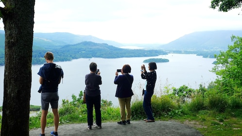 Tourists taking photos of lake from overlook in England