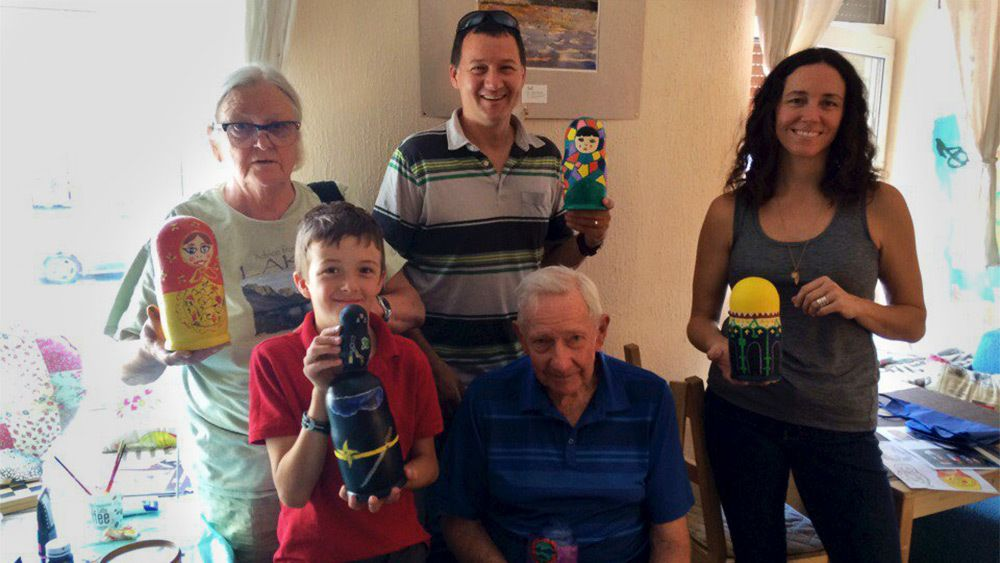 Multi-generation family holding hand painted nesting dolls in St Petersburg