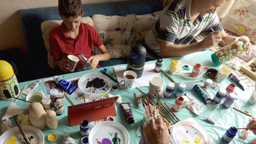 Father and son painting Matryoshka dolls in St Petersburg