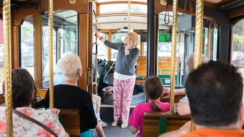 Tour guide talks to tourists while riding in trolley in Richmond